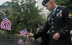 Medal of Honor recipient Staff Sgt. Ty Carter places a flag on a section of the 9/11 Memorial on Thursday, Aug. 29, 2013, in New York. (Photo courtesy AP Photo/Bebeto Matthews)