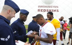 Washington Redskins players DeSean Jackson and Robert Griffin III sign autographs for military personnel after a summer workout. The team mascot has been under fire of activists and law makers. (AP photo)