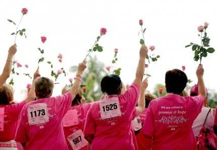 donne di spalle indossano tshirt rosa simbolo lotta tumore al seno e tengono in mano una rosa rivolta verso l'alto