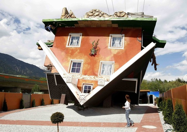 A woman walks around the back of a house, which was built upside down by Polish architects Irek Glowacki and Marek Rozhanski, in the western Austrian village of Terfens May 5, 2012. The project is meant to serve as a new tourist attraction in the area, and is now open for public viewing. Picture taken May 5, 2012. REUTERS/Dominic Ebenbichler