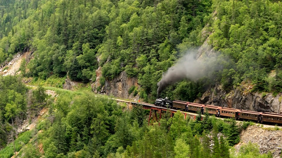 The White Pass and Yukon Railroad Baldwin Steam locomotive #73, climbing a steep grade as it leaves Skagway on it's round trip to Fraser, YT. Photo by Alan Vernon/Flickr