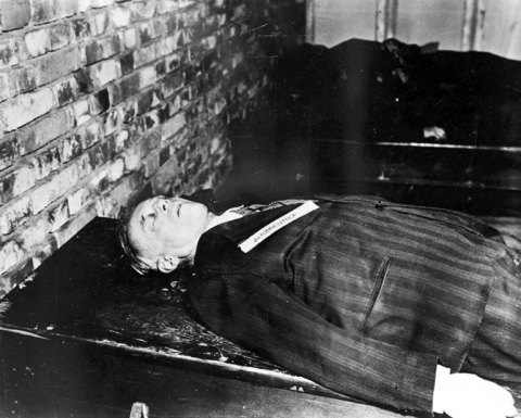 A corpse dressed in a black suit lies facing up on a table next to a brick wall. Only the upper torso is visible.