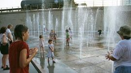 English: Children play in water fountains, in ...