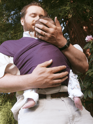 English: Father holding 7 week old baby in a h...