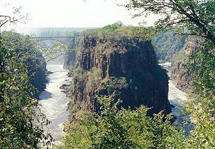 Victoria Falls' Second Gorge (with bridge) and Third Gorge (right). The peninsular cliffs are in Zambia, the outer cliffs in Zimbabwe.