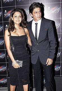 Shah Rukh Khan standing beside his wife Gauri at a party in 2012