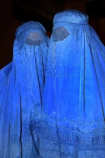 Women wearing burqas, the most concealing of a...