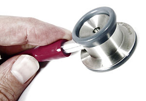 English: A stethoscope and partial hand.