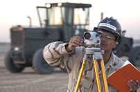 Surveyor at work with a leveling instrument.