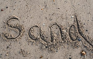 "The word ""sand"" written in sand"