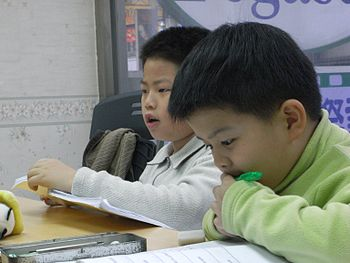 English: Two students studying English at a Ta...