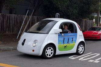 A white driverless car with a painting of people playing on monkey barks, and a female passenger.