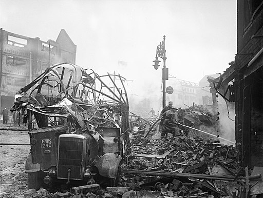 A wrecked bus stands among a scene of devastation in the centre of Coventry after the major Luftwaffe air raid on the night of 14-15 November 1940. H5593