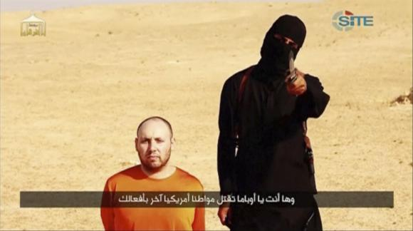 Still image from video shows a masked, black-clad militant, who has been identified by the Washington Post newspaper as Emwazi, standing next to a man purported to be Sotloff