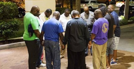 Worshippers gather to pray in a hotel parking lot across the street from the scene of a shooting June 17, 2015, in Charleston, S.C. (David Goldman AP)