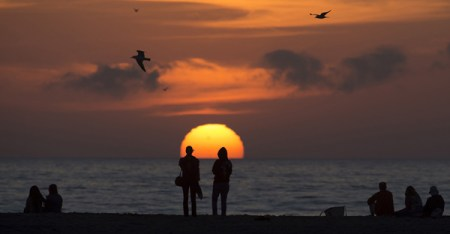 People sit on the beach and watch the sun set as seagulls fly overhead in Santa Monica, Calif. (Photo courtesy of REUTERS/Carlo Allegri)