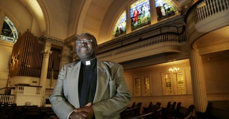 In this Dec. 6, 2016 photo, Pastor Abraham Waya poses inside the Central United Methodist Church in Brockton, Mass., after announcing the church will become an immigrant sanctuary. Hundreds of houses of worship representing an array of faiths around the country are offering to provide sanctuary for people who could face deportation if President-elect Donald Trump follows through on his campaign pledge. (AP Photo/Elise Amendola)