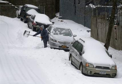 A man digs his car out along William Street during a snow storm, Tuesday, March 14, 2017, in New York. New York Gov. Andrew Cuomo has declared a state of emergency Tuesday for all of New York's 62 counties, including New York City's five boroughs. (AP Photo/Julie Jacobson)