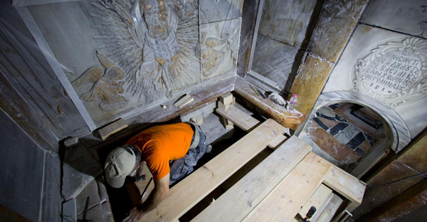 A conservator cleans the surface of the stone slab venerated as the final resting place of Jesus Christ. (PHOTOGRAPH BY ODED BALILTY, AP FOR NATIONAL GEOGRAPHIC)