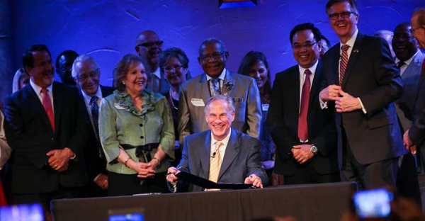 "Gov. Greg Abbott, accompanied by Lt. Gov. Dan Patrick and dozens of pastors including the ""Houston Five"" whose sermons were subpoenaed by the city of Houston, ceremonially signs Senate Bill 24 during the service on Sunday, May 21, 2017, at Woodlands Grace Church in The Woodlands. Texas Senate Bill 24 blocks religious sermons from being subpoenaed by governmental entities. (Michael Minasi)"