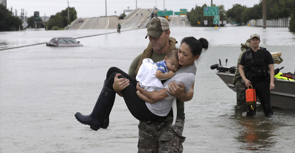 Houston Police SWAT officer Daryl Hudeck carries Catherine Pham and her 13-month-old son Aiden after rescuing them from their home surrounded by floodwaters from Tropical Storm Harvey in Houston on Sunday. The remnants of Hurricane Harvey sent devastating floods pouring into Houston Sunday as rising water chased thousands of people to rooftops or higher ground. David J. Phillip/AP