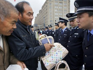 A Chinese citizen looks at a fake Louis Vuitton bag during a counterfeit goods awareness campaign run by the Shanghai Municipal Police I Photo: AP