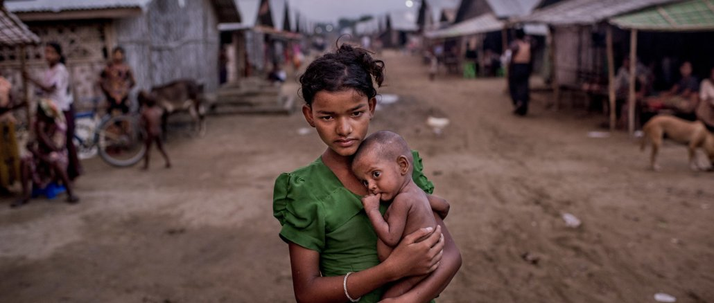 Oma Salema, 12, held her undernourished brother Ayub Khan, 1, at a camp for Rohingya in Sittwe, Myanmar   Source: New York Times