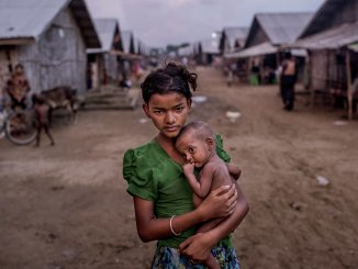 Oma Salema, 12, held her undernourished brother Ayub Khan, 1, at a camp for Rohingya in Sittwe, Myanmar | Source: New York Times