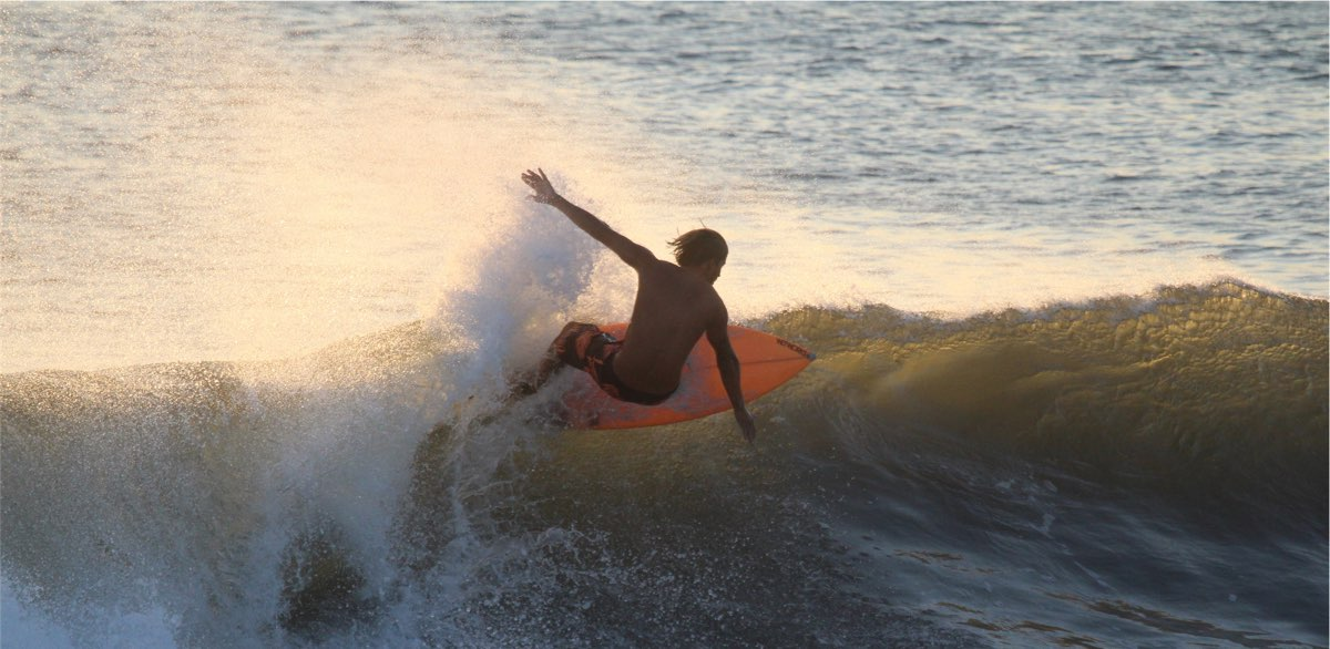 A surfer precariously perched on a wave.