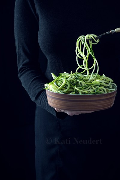 Frau hält Schüssel mit rohen Zucchinispaghetti.
