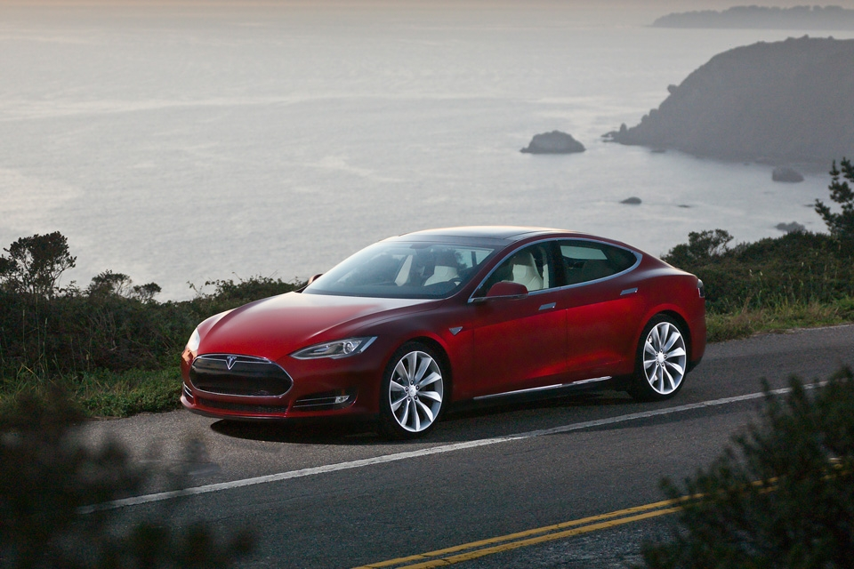 A Tesla Model S against a gorgeous ocean backdrop