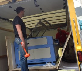 "Roth and business partner Matt Stollenwerk unload a laser cutter for new business ""SF Laser."""