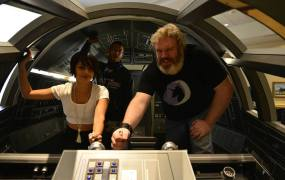Game of Thrones actors Amrita Acharia (IRRI) and  Kristian Nairn (aka Hodor) take a picture inside the cockpit of the Full-Scale Falcon project's Millennium Falcon model.