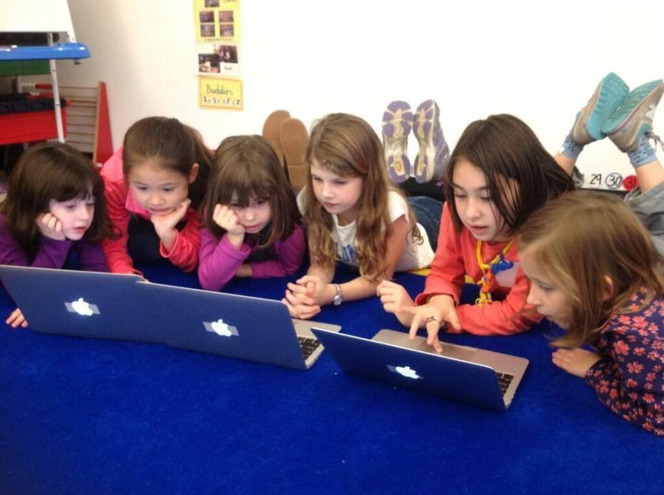Fourth grade girls teach kindergartners during Hour of Code.