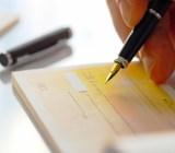 Signing checkbook JJ Studio shutterstock