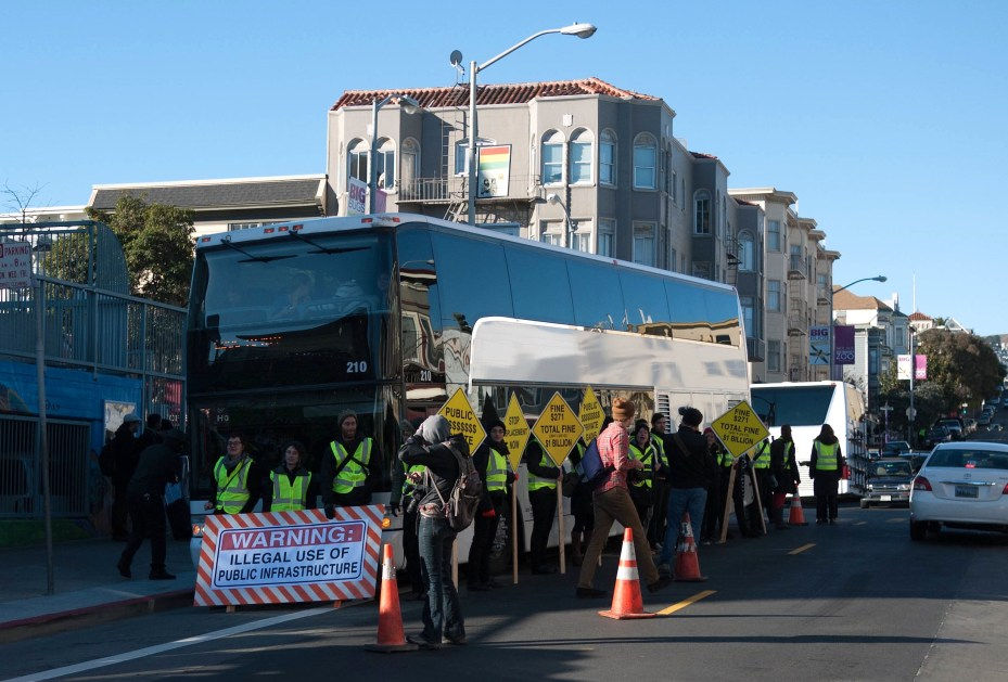 "Protestors block a ""Google Bus"" in San Francisco."