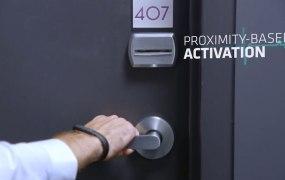 A man unlocks a hotel room door with Bionym's Nymi ID bracelet.