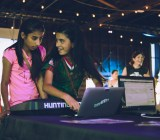 Two girls work on some music, or some code, or both, at the STEAM Carnival.
