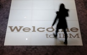 A woman walks over a welcoming sign at the booth of IBM at the CeBIT trade fair in Hanover March 15, 2015. The world's biggest computer and software fair will open to the public from March 16 to 20.