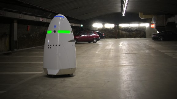 A Knightscope K5 robot patrols an empty parking lot.