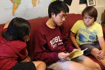 Stanford student Chester Thai reads to two third grade students.