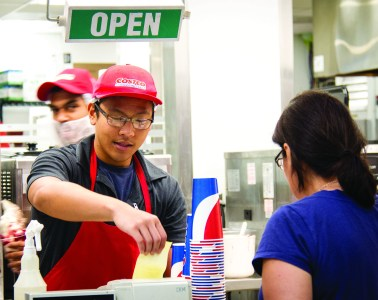 A Costco employee smiles as he hands a customer her receipt of her purchse. Photo by Emma Cockerell