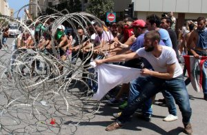 epa04894121 Lebanese activists try to remove barbed wire blocking the entrance to the Lebanese Government Palace during a protest against the ongoing garbage crisis, downtown Beirut, Lebanon, 23 August 2015. According to local reports, Lebanese citizens gathered to protest the government's ongoing inability to find a solution to the country's ongoing garbage crisis, which has left streets overflowing with garbage, due in large part to graft associated with the awarding of contracts to private companies linked to the Government to operate collections. EPA/WAEL HAMZEH