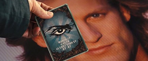 In the back of the card is the symbol of the All-Seeing Eye with invitation information. In this particular shot, the card is hiding one of Merritt McKinney's eyes (played by Woody Harrelson), hinting that he's about to be part of the occult elite's entertainment industry.
