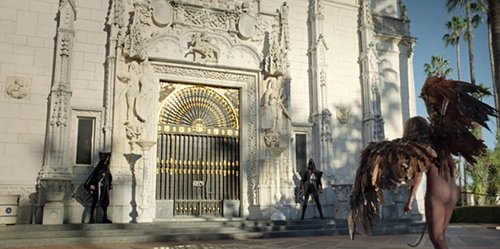 Lucifer-Gaga arrives in front of the Hearst Castle and is greeted by hooded men.