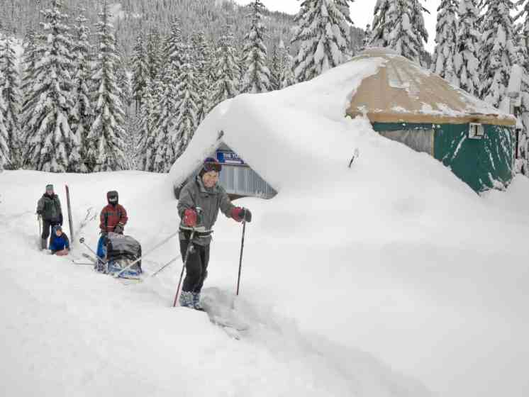 A happy family skis from the Mount Tahoma Trails yurt after a snow-filled adventure. © Ed Book Photo
