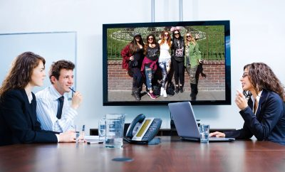 Happy man women businesspeople having meeting in boardroom at office in front of a huge plasma TV screen, indoor, smiling.VIVA GLAM Magazine team on TV screen, Top Mistakes Grad make when entering the workforce