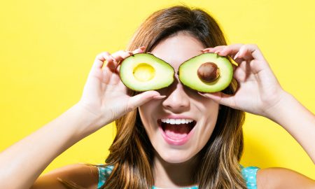 Happy young woman holding avocado halves