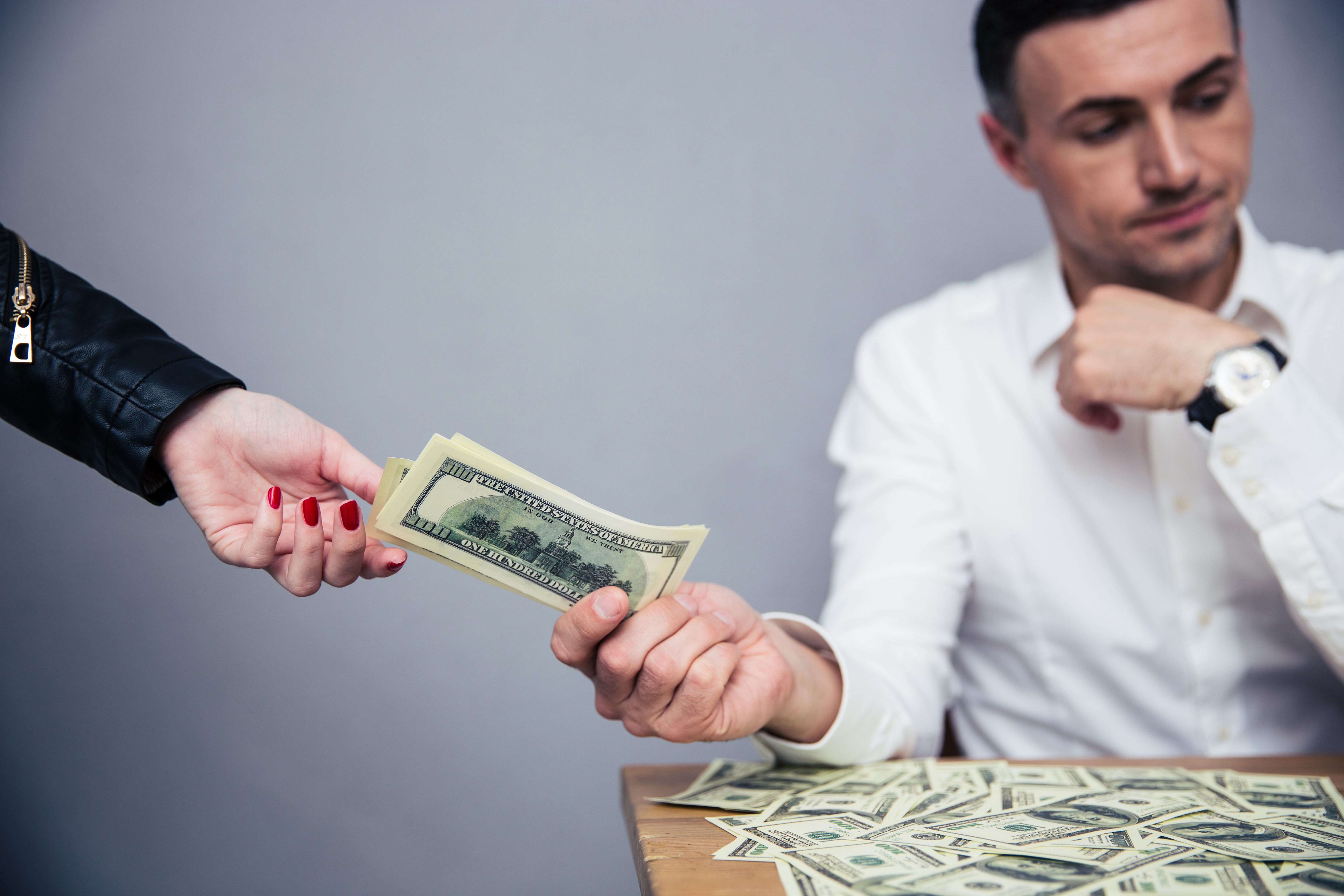 Unhappy man giving money to woman over gray background