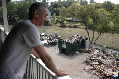 Adam Adler looks out from his veranda overlooking the Ottauquechee River at a wasteland of debris behind The Parker House, the B&B he owns with his wife Alexandra. VTD/Andrew Nemethy